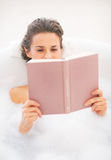 Young woman reading book in bathtub Royalty Free Stock Images