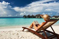 Young woman reading a book at beach Stock Photos