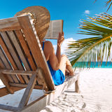 Young woman reading a book at beach. Young woman reading a book at the beach Stock Photo