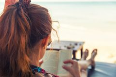Young woman reading a book at beach. Young woman reading a book at the beach Stock Image