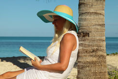 Young woman reading a book at beach. Young woman reading a book at the beach Stock Photography