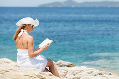 Young woman reading book on the beach. Young beautiful woman reading book and relaxing on the beach Royalty Free Stock Image