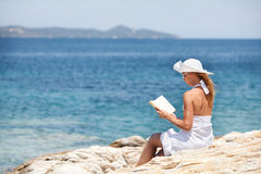Young Woman Reading Book On The Beach. Young beautiful woman reading book and relaxing on the beach Stock Photos