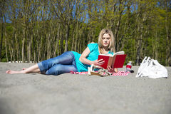 Young Woman Reading Book On Beach Royalty Free Stock Photos