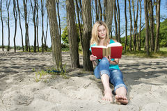 Young Woman Reading Book On Beach Stock Photography