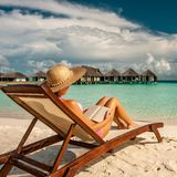 Young woman reading a book at beach. Young woman reading a book at the beach Royalty Free Stock Photo