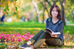 Young woman reading a book in beautiful autumn Royalty Free Stock Photos
