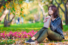 Young woman reading a book in beautiful autumn Stock Photo