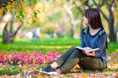 Young woman reading a book in beautiful autumn Stock Images