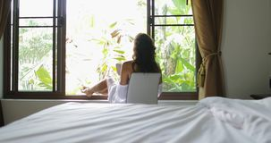 Young Woman Reading Book Beautiful Girl Morning Sitting In Bedroom Over Big Window With View On Tropical Garden. Slow Motion 60 stock footage