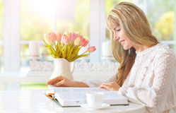 Young woman reading book. Beautiful young woman reading book on light cozy kitchen Royalty Free Stock Images