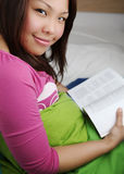 Young woman reading a book in bed Royalty Free Stock Photography