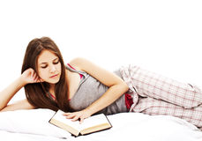 Young woman reading book in bed Stock Image