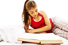 Young woman reading book in bed Stock Photos