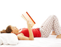 Young woman reading book in bed Royalty Free Stock Photo