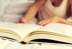 Young woman reading a book in bed Royalty Free Stock Photo