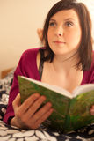 Young woman reading a book in bed Royalty Free Stock Images