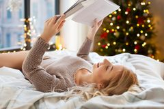 Young woman reading book in bed at home stock image