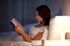 Young woman reading book in bed at night home Stock Photo