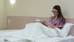 Young woman reading book in bed before sleep and laughing. Professional shot in 4K resolution. 068. You can use it e.g. in your commercial video, business royalty free stock image