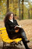 Young woman reading book on bench Royalty Free Stock Image