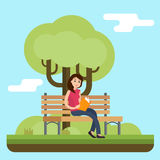 Young woman reading book on bench in park. Royalty Free Stock Photography