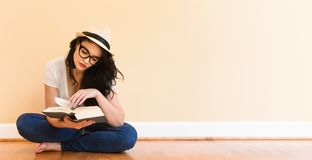 Young woman reading a book. In a big room stock image