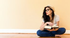 Young woman reading a book. In a big room Stock Photography