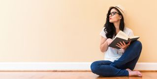 Young woman reading a book. In a big room royalty free stock photo