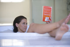 Young woman reading book in bubble bath Royalty Free Stock Photos