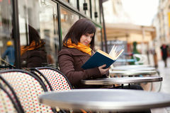 Young woman reading a book in cafe Stock Images