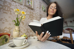 Young woman reading book in cafe Royalty Free Stock Image