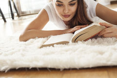 Young woman reading book on capet Royalty Free Stock Photo