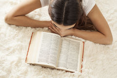 Young woman reading book on capet Stock Images