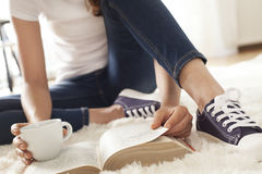 Young woman reading book on capet Stock Photography
