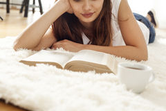 Young woman reading book on carpet Royalty Free Stock Images