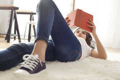 Young woman reading book on carpet Stock Image