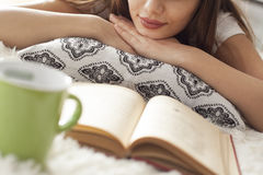 Young woman reading book on carpet Stock Photo