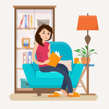 Young woman reading book on chair at home. Stock Photo