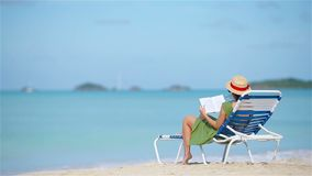 Young woman reading book on chaise-longue on tropical white beach