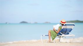 Young woman reading book during tropical white beach. Young woman reading book on chaise-longue on tropical white beach stock video