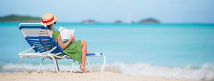 Young woman reading book on chaise-lounge on the beach Stock Image