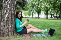 Young woman reading a book in the city park Stock Images