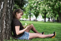 Young woman reading a book in the city park Stock Photography