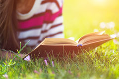 Young woman reading book in city park at summer day.  Royalty Free Stock Photo