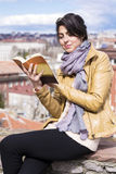 Young woman reading a book on a cityscape background Royalty Free Stock Photos