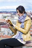 Young woman reading a book on a cityscape background Stock Photography