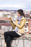 Young woman reading a book on a cityscape background Stock Photo