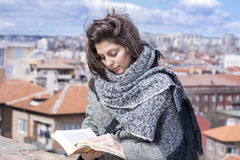 Young woman reading a book on a cityscape background Royalty Free Stock Images