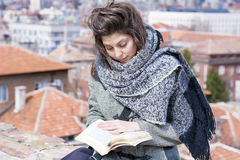 Young woman reading a book on a cityscape background Royalty Free Stock Image